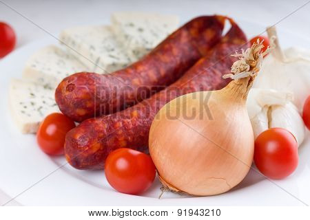Onion And Tomatoes With Sausages On White Plate