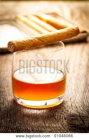 Cuban cigars on wooden table with glass of rum