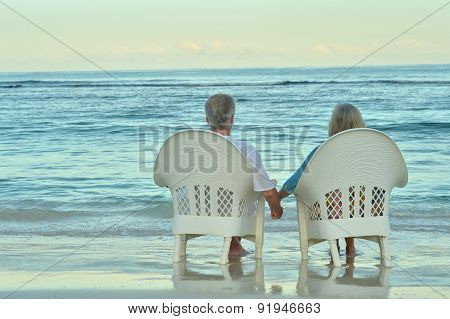 Elderly couple sitting on the shore