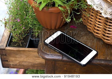 Template. Phone on a wooden table, around the flowers in the baskets.