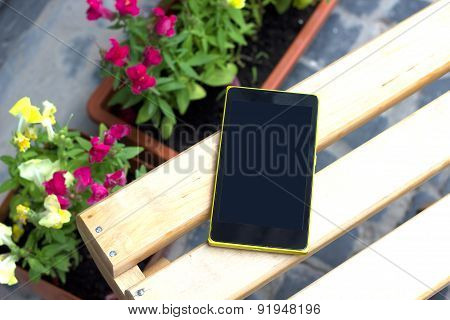 Template. Phone on a wooden table, around the flowers