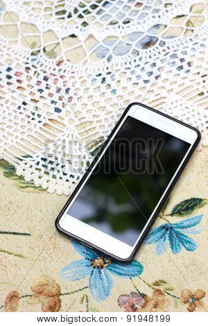 Phone on the tablecloth with flowers