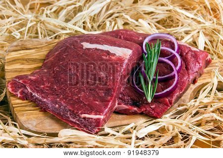 British Beef Flat Iron steak on cutting board and straw, rosemary and onion