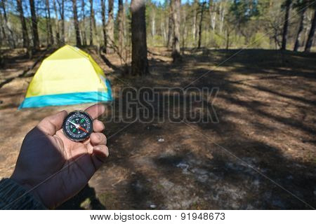 Compass in the woods against the tent.
