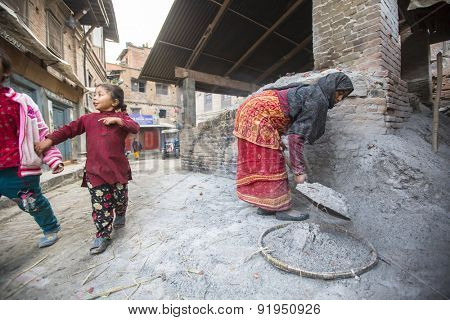 BHAKTAPUR, NEPAL - CIRCA DEC, 2013: Unidentified Nepalese woman working in the his pottery workshop. More 100 cultural groups have created an image Bhaktapur as Capital of Nepal Arts.
