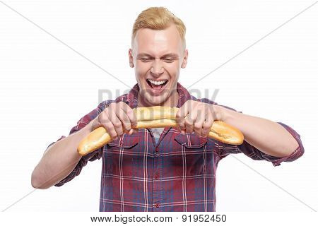 Smiling man breaking long loaf