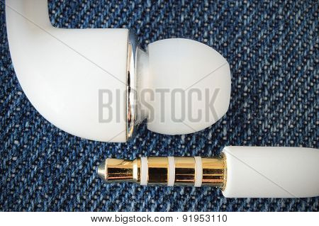 White earphones and connector on jeans fabric background. Macro