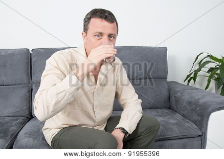 Picture Of A Happy Man Sitting On Couch In House Drinking