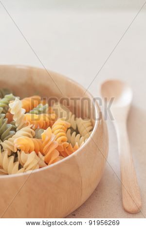 Raw Fusilli Pasta On Wooden Bowl