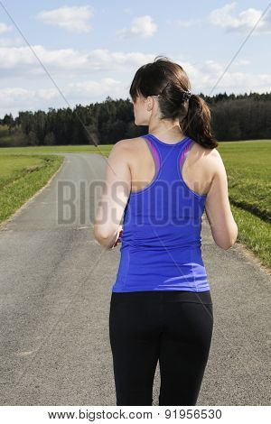 Backside Of A Young Woman Jogging Outdoors