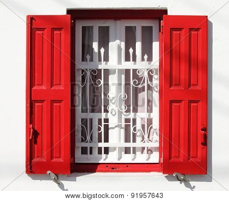 Window with grille and red shutters