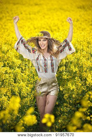 Young girl wearing Romanian traditional blouse posing in canola field with cloudy sky in background,