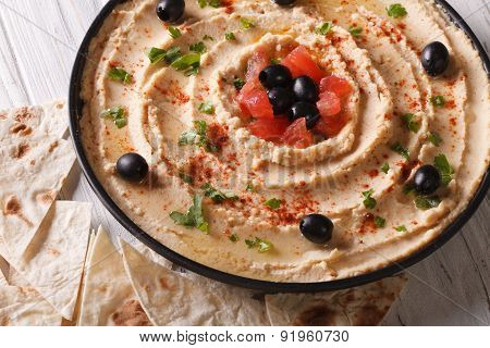 Hummus With Olives, Tomatoes And Herbs Close-up. Horizontal