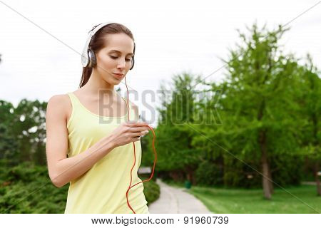 Young sportive woman choosing music in park
