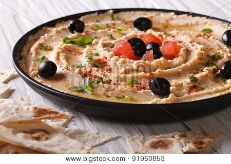 Hummus With Olives And Herbs On A Plate Close-up. Horizontal