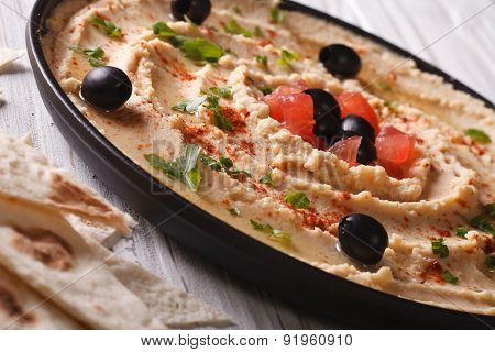 Hummus With Olives And Tomatoes On A Plate Close-up.
