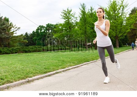 Portrait of woman running in park