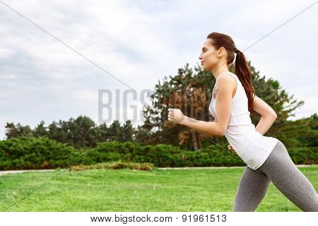 Profile of running woman in park