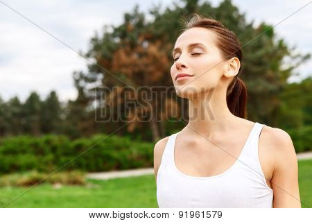Pretty girl with closed eyes in park