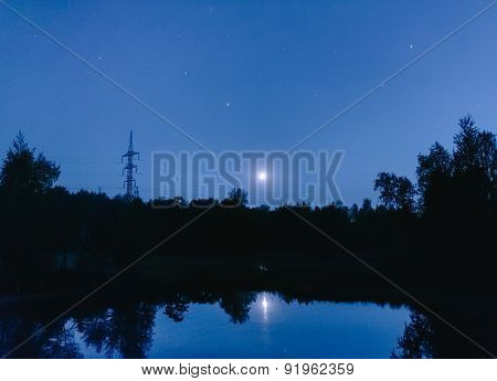 Metal Electric Poles In The Moonlight At The Lake