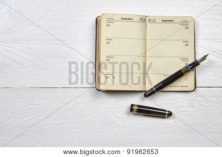 Antique Fountain Pen And Old Calendar On A White Wooden Table