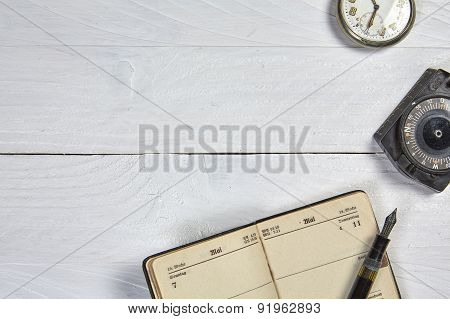 Antique Fountain Pen, Old Calendar, Watch And Compass On A White Wooden Table