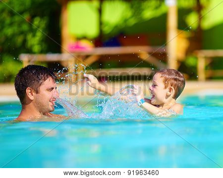 Happy Father And Son Dabbling In Pool Water, Summer Holiday