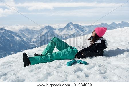 Beautiful young woman laying in the snow mountains