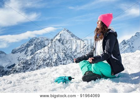 Beautiful young woman doing yoga in the snow mountains