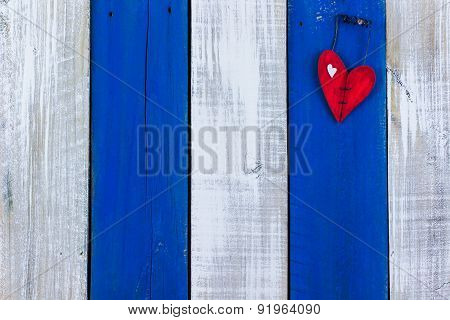 Red heart hanging on antique blue wooden fence