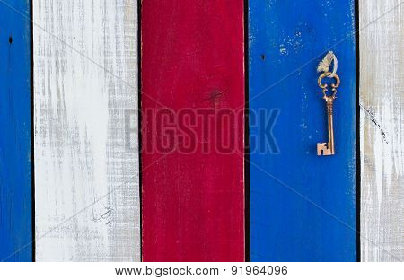 Skeleton key hanging on wooden fence