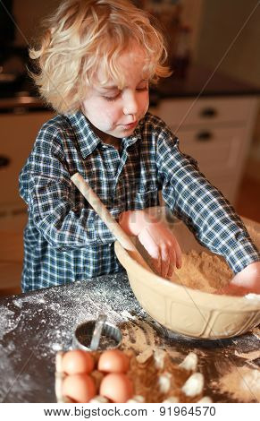 Little Boy Mixing Flour In A Bowl