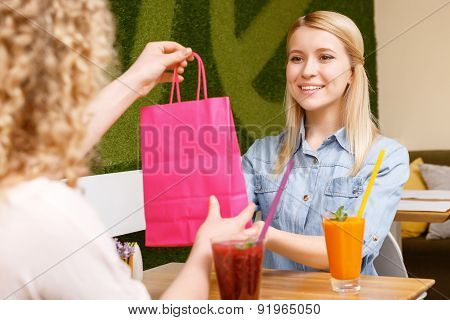 Pretty young woman getting present in cafe