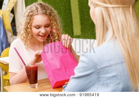 Girl looking inside bag in cafe