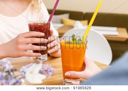 Close up of women holding cocktails