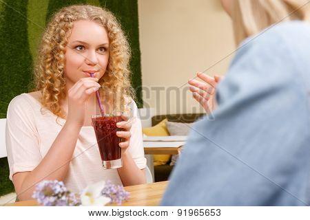 Girls drinking cocktail through straw