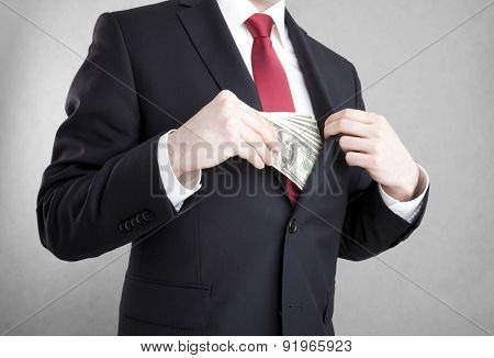 Corruption. Man putting polish money in suit jacket pocket.