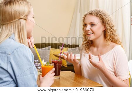 Two girls having conversation in cafe