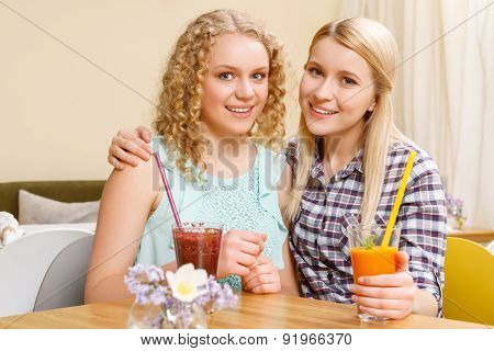 Two smiling girls in cafe