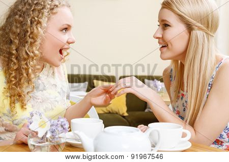 Smiling woman showing wedding ring in cafe