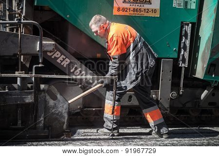 Asphalting In Progress, Worker With A Shovel
