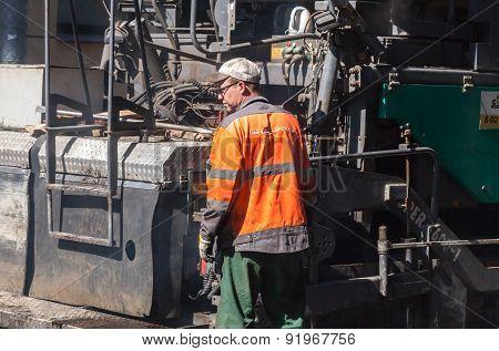 Operator Walks On Dirty Paver Machine