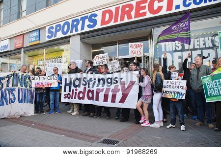 HASTINGS, ENGLAND - MAY 30, 2015: Protestors demonstrate against zero hour contracts outside a branch of the Sports Direct sports shop after an anti austerity march through the town.