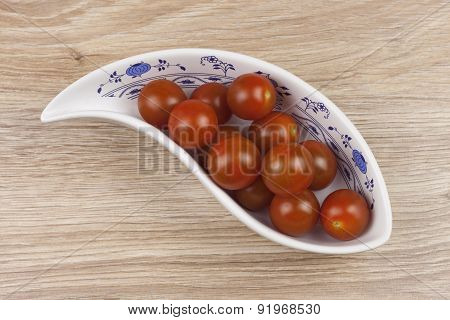 Sherry tomatoes in a porcelain bowl on wooden background, healthy eating