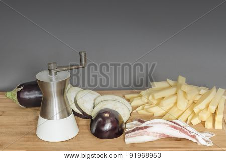Bacon with fresh eggplant and potatoes on wooden background