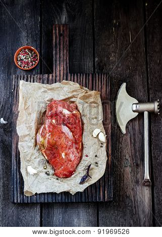 Raw Meat With Garlic And Axe On Wooden Table.