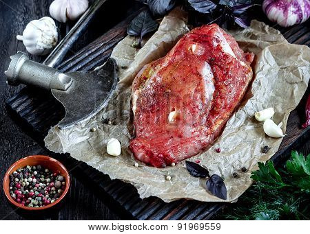 Raw Meat With Garlic And Herbs And Axe On Wooden Table. Style Rustic. Selective Focus.