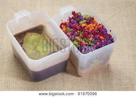 colorful juicer pulp and fresh juice after juicing raw vegetables (carrot, red beat, cucumber, kale, red cabbage) - plastic cups against burlap canvas background