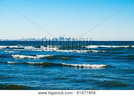 Waves Breaking On Lake With Toronto Skyline In Distance.