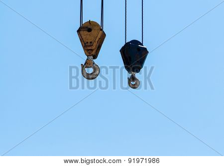Pair Of Hanging Industrial Crane Hoists On Pale Blue Sky.